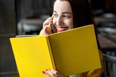 有书和手机的妇女 免版税库存照片