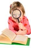 有书和放大镜的女孩 免版税库存照片