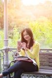 有书和文件的女性大学生在膝部,按在她的电话按 库存图片