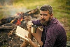 有书和杯子的行家远足者在自然的篝火 免版税库存图片