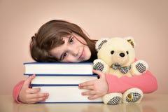 有书和玩具熊的女孩 免版税图库摄影
