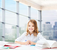 有书和笔记本的愉快的女孩在学校 库存照片