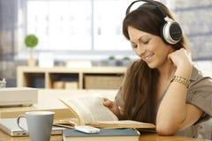有书和耳机的愉快的妇女 免版税库存图片