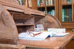 有书和膝上型计算机的经典古色古香的木书桌 免版税图库摄影