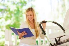 有书和婴儿推车的愉快的母亲在公园 免版税图库摄影