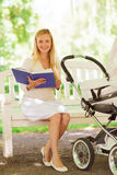 有书和婴儿推车的愉快的母亲在公园 库存照片