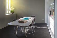 有书架和一张白色桌的,五把椅子家庭书库 免版税库存照片