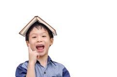有书的亚裔男孩在顶头认为 免版税库存照片