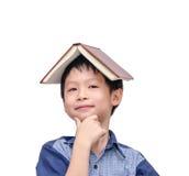 有书的亚裔男孩在顶头认为 图库摄影