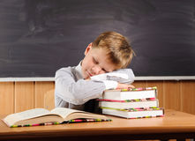 有书的休眠的男孩在服务台 免版税库存照片