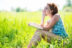 有书的俏丽的微笑的妇女在自然 免版税库存照片
