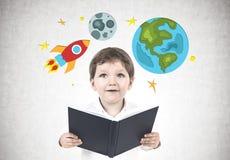有书的可爱的小男孩,太空旅行 图库摄影