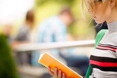 有书的女孩反对人背景坐长凳 免版税库存照片