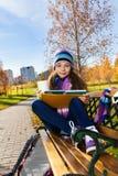 有书的女孩在学校以后在公园 库存图片