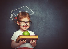 有书的女孩在校务委员会的女小学生和苹果 免版税库存照片