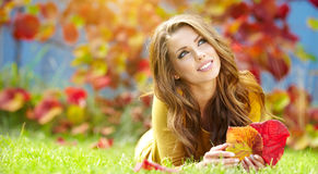 有书的女孩在秋天公园 免版税库存照片