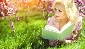 有书的女孩 说谎在草的白肤金发的少妇 图库摄影