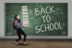 有书的女小学生回到学校 免版税库存图片