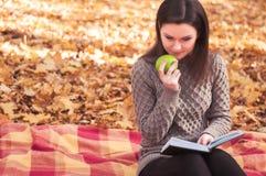 有书的妇女和苹果坐地毯 免版税库存图片
