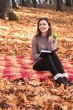 有书的妇女和苹果坐地毯 免版税库存照片
