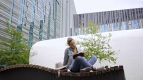 有书的妇女在大厦附近的长凳 股票视频