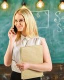 有书的妇女谈话在手机在教室 解决在电话,黑板的微笑的面孔的老师问题  库存照片