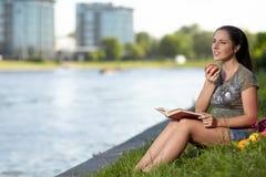 有书的孕妇在公园坐 库存图片