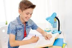 有书的学生男孩在家写给笔记本的 免版税库存照片