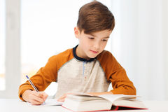 有书的学生男孩在家写给笔记本的 库存图片