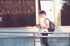 有书的学生走在大学前面的  库存图片
