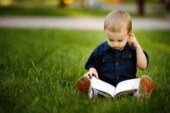 有书的小愉快的男孩 免版税库存图片