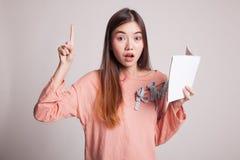 有书的年轻亚裔妇女有一个想法 库存照片