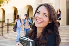 有书的微笑的混合的族种女孩走在校园里的 免版税库存照片