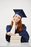 有书的微笑美丽的女性的毕业生看照相机 奶油被装载的饼干 库存照片
