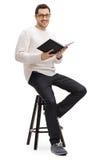有书的快乐的人坐椅子 免版税库存照片