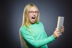 有书的恼怒或被注重的女孩 特写镜头画象英俊青少年在灰色背景 研究概念 免版税库存图片