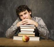 有书的情感学生和红色苹果在教室,黑板的 库存图片