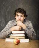 有书的情感学生和红色苹果在教室,黑板的 免版税图库摄影