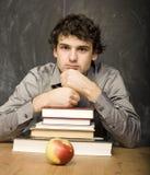 有书的情感学生和红色苹果在教室,黑板的 库存照片