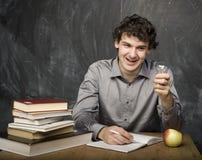 有书的情感学生和红色苹果在教室,黑板的 免版税库存照片