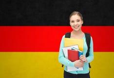 有书的愉快和微笑的少年学生女孩 免版税库存照片