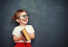 有书的愉快的女孩女小学生从黑板 免版税库存图片