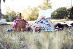 有书的愉快的妇女微笑本质上的 免版税库存照片