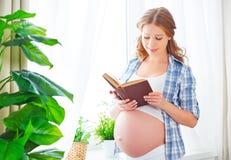 有书的愉快的孕妇在窗口 免版税库存图片