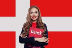 有书的愉快的年轻女人学生反对丹麦旗子背景,旅行并且学会丹麦语言概念 免版税库存照片