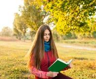 有书的愉快的年轻少年在秋天公园 库存照片