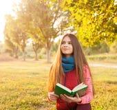 有书的愉快的年轻少年在秋天公园 库存图片