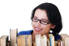有书的愉快的微笑的新学员妇女 免版税库存照片
