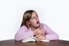 有书的打呵欠的女孩在白色背景 免版税库存图片
