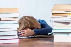 有书的睡觉的女孩在白色背景 库存图片